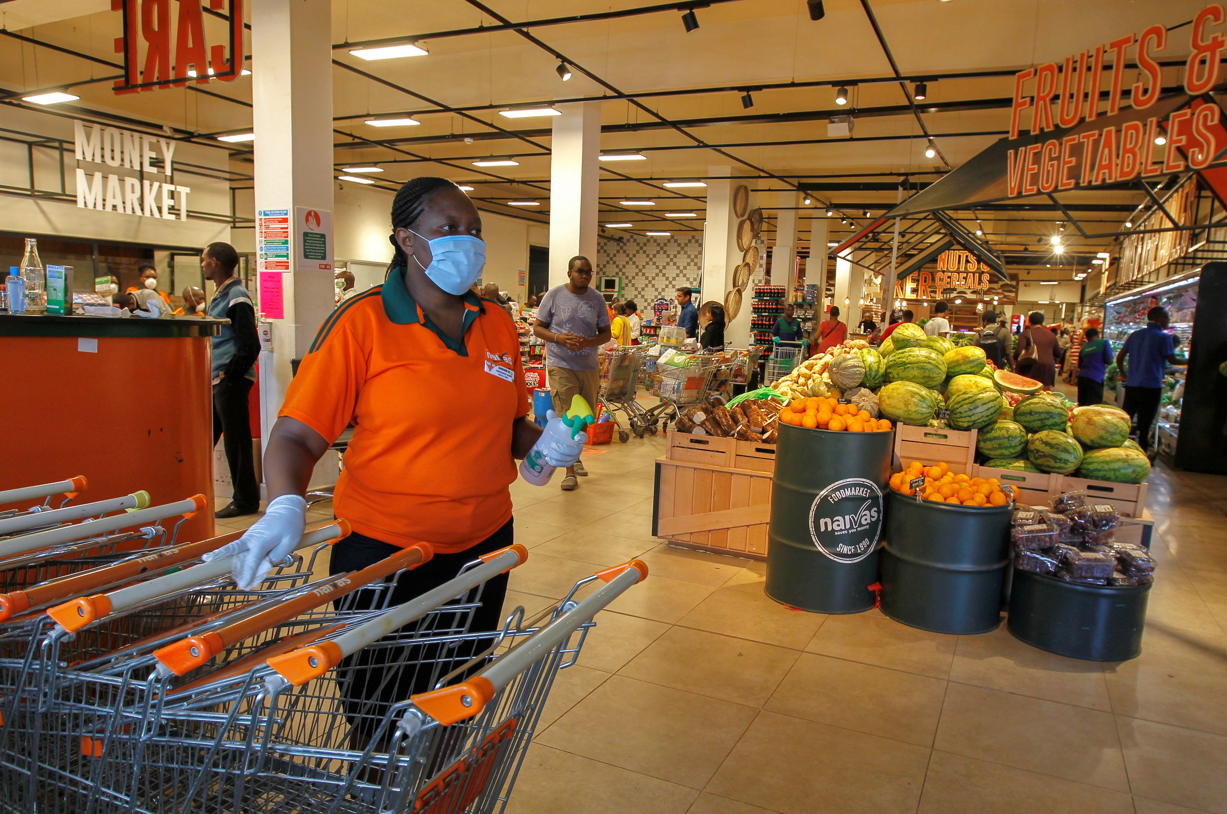 A worker disinfects shopping trolleys as customers shop in the Naivas Supermarket, to stock their homes amid concerns about the spread of coronavirus disease (COVID-19) in Nairobi, Kenya March 23, 2020. REUTERS/Njeri Mwangi